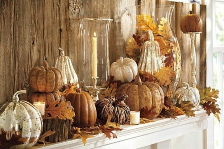 a neutral and rustic Thanksgiving mantel with tree stumps, fall leaves, pumpkins stacked and gourds, candles in a vase and an oversized vase with leaves