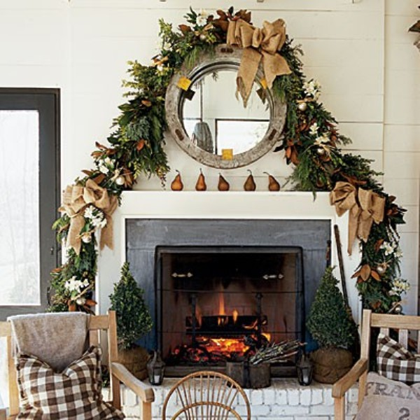 a fall to Christmas mantel with pears and a lush greenery and magnolia leaf garland plus a large burlap bow is a lovely idea