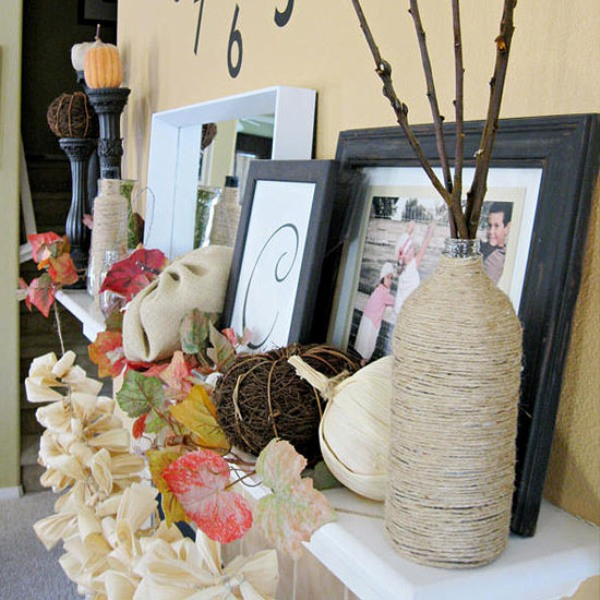 a vintage Thanksgiving mantel with bold faux leaves, a burlap garland, faux pumpkins of various materials and branches in a twine wrapped vase