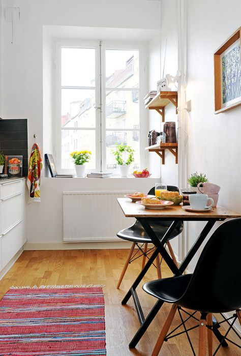 a tiny dining space in a Scandinavian kitchen, with a small folding table and black chairs, open shelves and an artwork