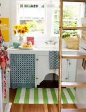 a tiny cottage kitchen with white cabinets, printed colorful texitles, a ladder for storing things up and on it