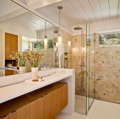 a warming mid-century modern bathroom with earthy tiles, a wooden cabinet under the vanity countertop and large mirrors
