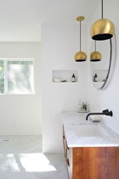 an elegant neutral mid-century modern bathroom with tiles and stone, a stained vanity and gold pendant lamps over the vanity