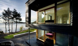 Twofold House In Black Stained Wood With Natural Wood Between The Window Partitions
