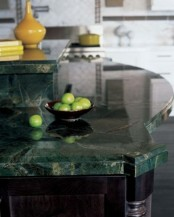 dark cabinets and green stone countertops create a chic moody look in the kitchen