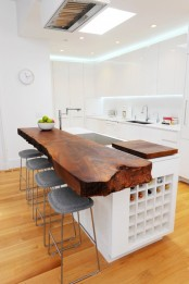 a modern sleek kitchen island with a rich stained countertop with a living edge for a contrasting look