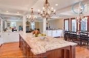 white cabinets with light-colored stone countertops and a rich stained kitchen island with a grey stone countertop