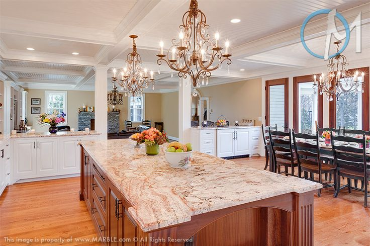 white cabinets with light colored stone countertops and a rich stained kitchen island with a grey stone countertop