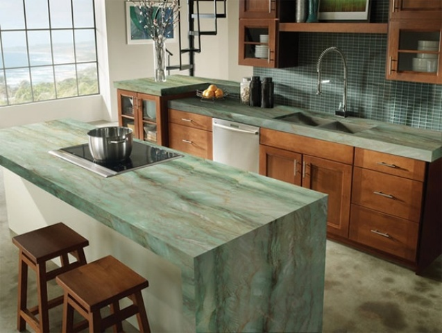 rich stained wooden cabinets with green stone countertops and the same waterfall countertop on the kitchen island