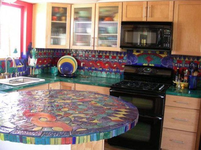 a colorful mosaic countertop adds brightness to the space and spruces up neutral wooden cabinets