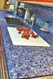 a bright blue mosaic countertop contrasts the warm shade of wood and makes the kitchen bold