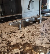 a dark stone countertop with light-colored and dark wooden cabinets make up a bold and creative kitchen look