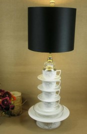 a black table lamp with a base made of teaware and a sleek black lampshade is a cool idea with a quirky feel, reminds of Alice in Wonderland