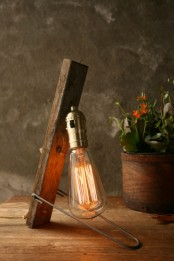 an industrial table lamp of a rough wooden piece, metal and a large bulb is a bold industrial statement for your space