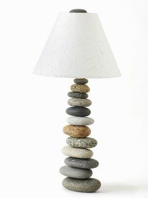 a coastal table lamp with a base made of pebbles and a white lampshade for a beach or coastal house