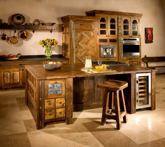 a large dark stained wood kitchen island with drawers and drink coolers matches the kitchen and looks very cozy