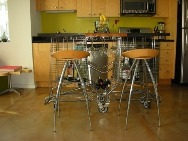 a strange looking kitchen island of metal on casters and with a wooden tabletop contrasts the simple and modern plywood kitchen