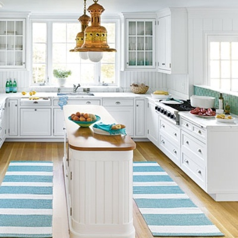 a white shiplap kitchen island with a wooden countertop features a unique shape and looks very fresh
