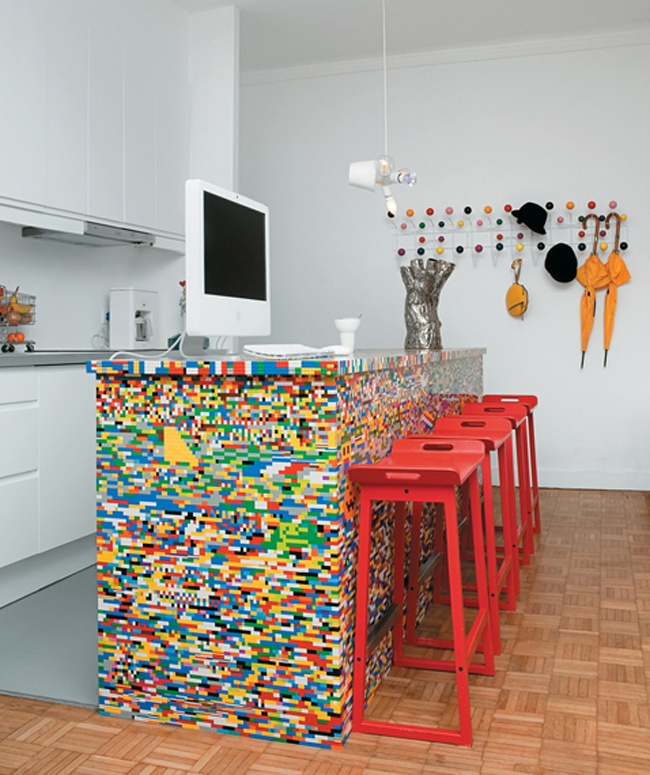 a colorful Lego kitchen island and bright red stools make a statement in the neutral kitchen and spruce it up