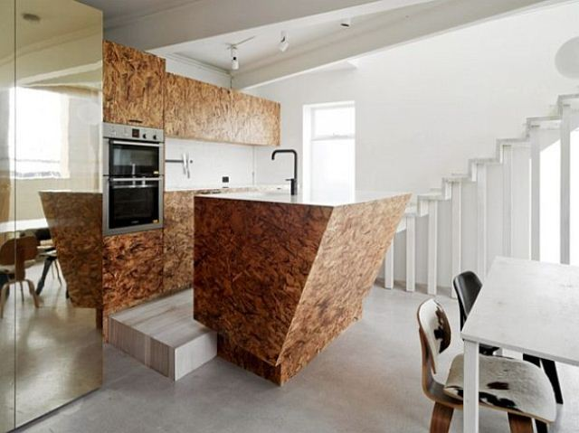 a sculptural geometric plywood kitchen island with hidden storage space stands out with its amazing shape and lines