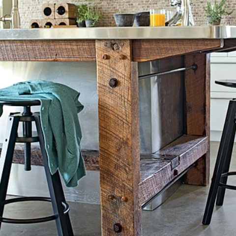 an industrial kitchen island of rough wood and a metal tabletop features soem storage space inside