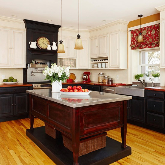 a redwood kitchen island on a platform with a metal countertop stands out in a black kitchen and features open storage space