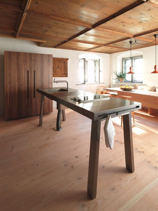 a contemporary wood and metal kitchen island designed as a table to look more lightweight, with a sink and some holders