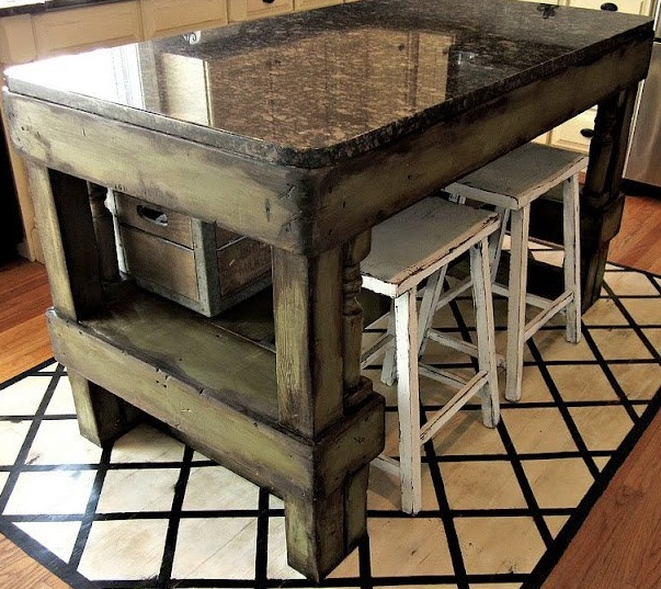 a shabby dark stained wood kitchen island with a polished stone tabletop will give much space for cooking and even for eating