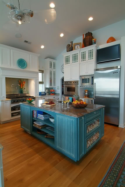 a bright blue vintage kitchen island with a stone countertop, open and closed storage compartments