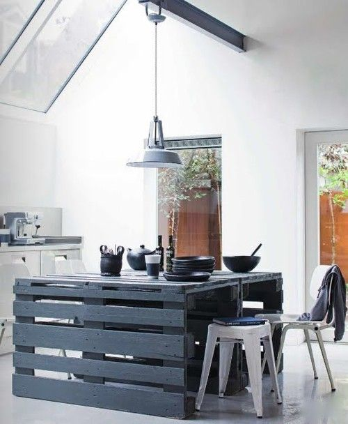a slate grey pallet kitchen island with some eating space and cooking, too, stands out in a neutral kitchen