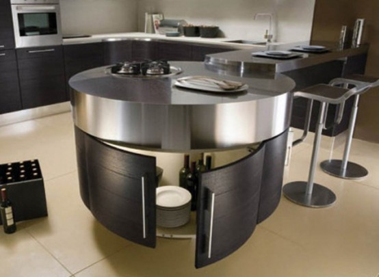 a round kitchen island of dark stained wood and metal on top plus an additional counter that can serve a breakfast bar or a drink one