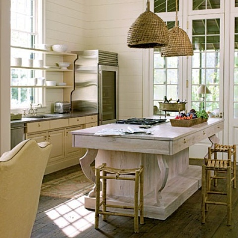 a large whitewashed wooden kitchen island stands out with its color and finish and adds a relaxed feel to the space