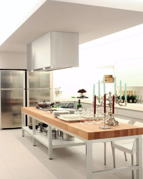 an oversized contemporary kitchen island with a metal base and a butcherblock countertop can be used for cooking and eating there