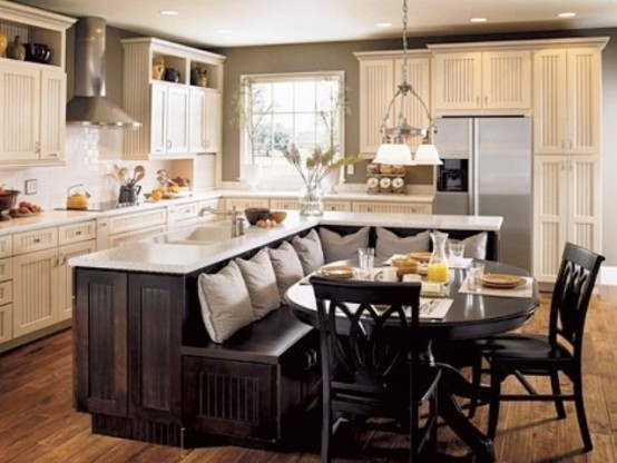 an oversized dark stained L-shaped kitchen island with a built-in bench and white countertops will save much space and give you everything you need