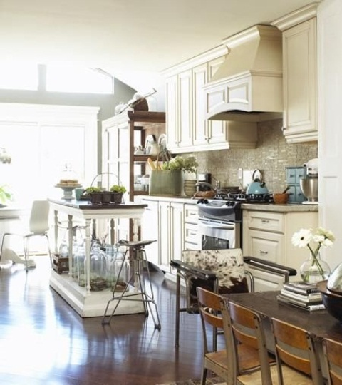 a vintage white kitchen island with carved out legs and a dark countertop looks very lightweight and elegant