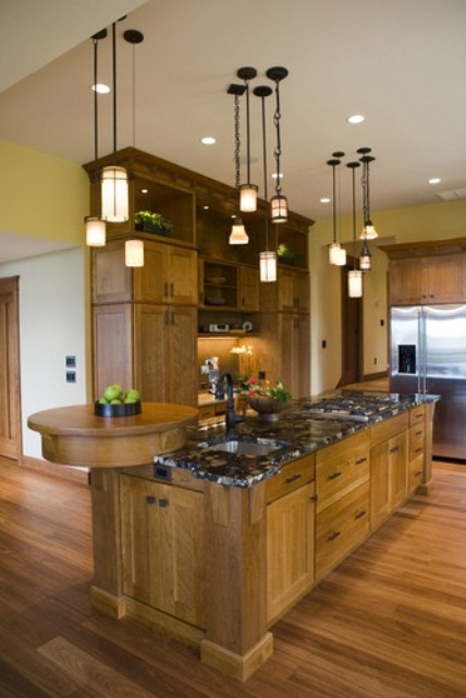 an oversized rustic kitchen island with much storage space, a stone countertop and a round wooden board for cutting or displaying