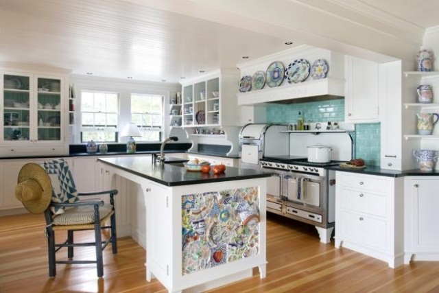 a usual black and white kitchen island is made unique with colorful mosaics on the side