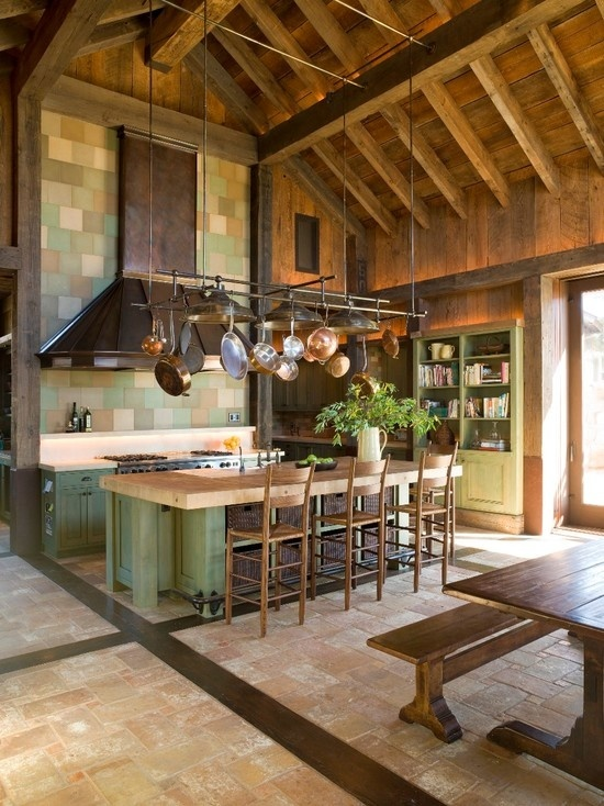 a green kitchen island with a butcherblock countertop hides some basket drawers inside and adds a rustic feel