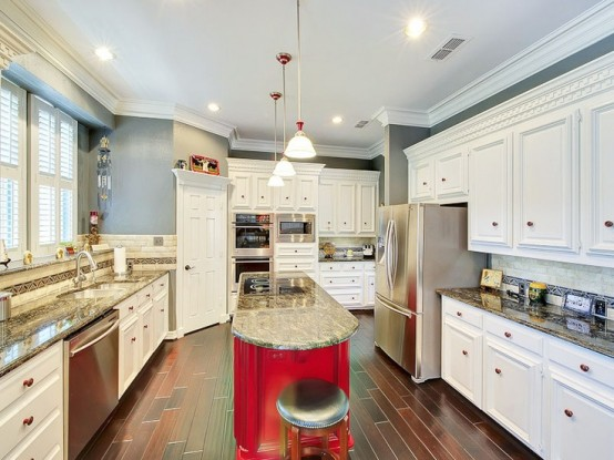 a long curved hot red kitchen island with a stone countertop is a great idea for  anarrow kitchen, it won't take much space