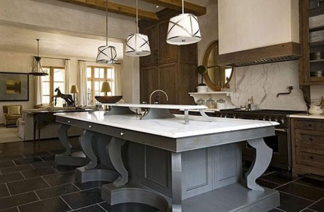 a large vintage grey kitchen island with a white stonr countertop and an additional raised one for storage