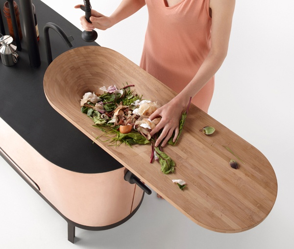 a curved sleek kitchen island with a black countertop and an additional cutting board on top is a gorgeous option for a minimalist space