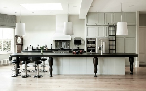 a white kitchen island covered with a large black table to elongate it and make it more functional