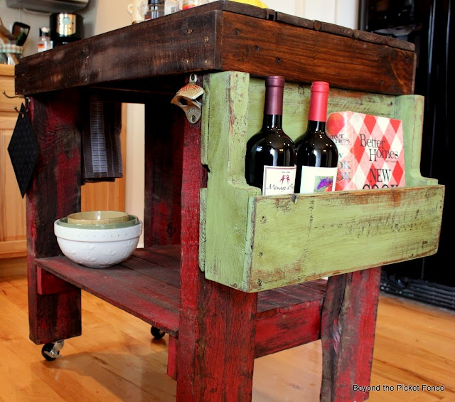 a shabby chic dark stained and red kitchen island on casters plus a green wooden box for storage