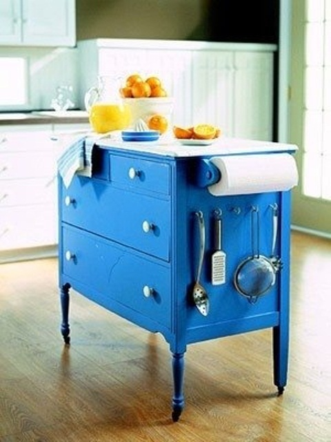 a bright blue vintage dresser on casters with a white countertop and some hangers is a bold and statement idea to rock