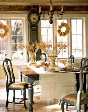 a vintage rustic Thanksgiving tablescape done with a burlap runner, wheat in vases and a tray with nuts, acorns and large candles as a centerpiece