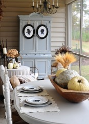 a neutral vintage and rustic Thanksgiving tablescape with lace placemats, printed plates, a wooden bowl with wheat and neutral pumpkins