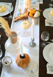 a vintage Thanksgiving tablescape with a brown tablecloth and neutral linens, white candles, natural pumpkins, wheat and driftwood candleholders