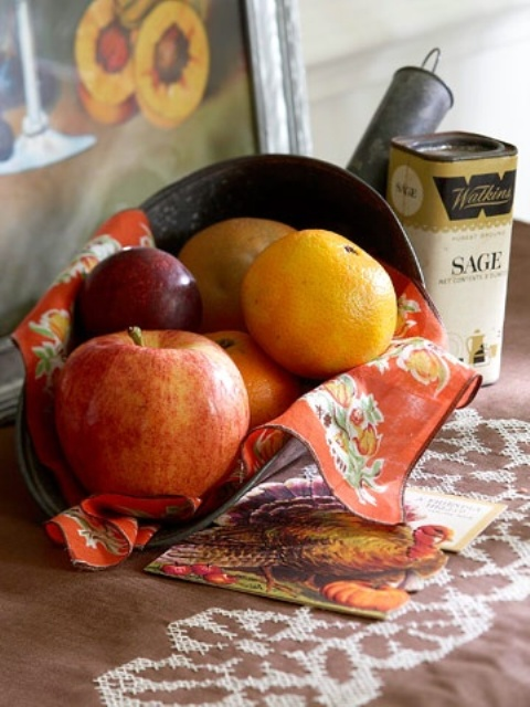 a vintage metal shovel with faux pumpkins and fruits and a bright napkin is a nice vintage decoration for Thanksgiving