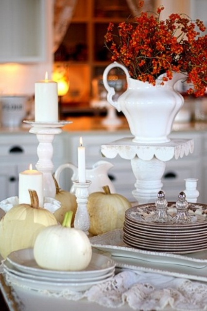 beautiful vintage Thanksgiving tablescape with neutral pumpkins, white porcelain, white candles and dried flowers in a jug, vintage plates