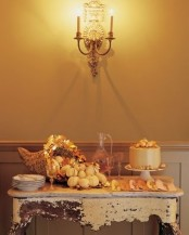a vintage rustic Thanksgiving dessert table with a woven cornucopia with leaves, mini pumpkins and a refined shabby chic table